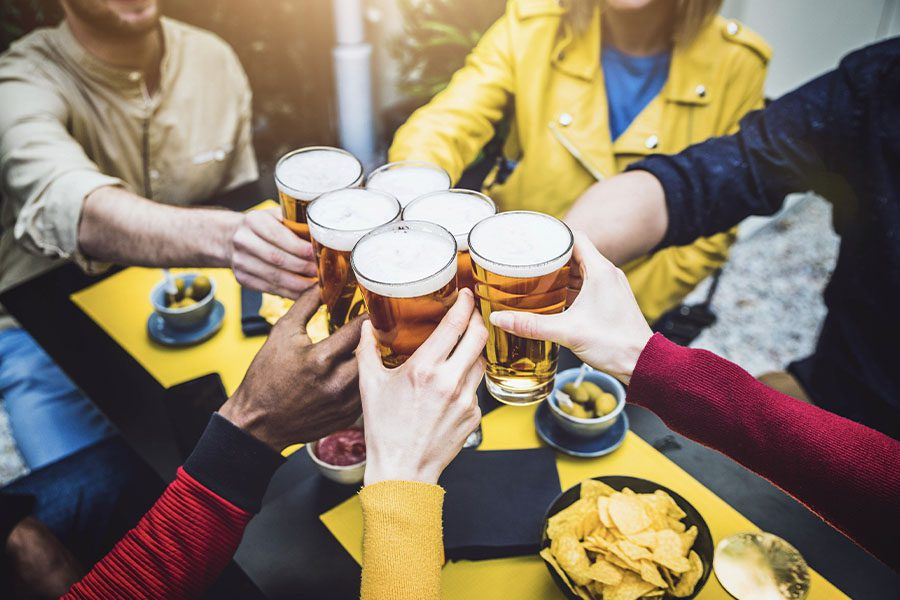 Specialized Business Insurance - A Group of Friends Having Fun and Toasting Beer at a Brewery with a Focus On Their Drinking Glasses