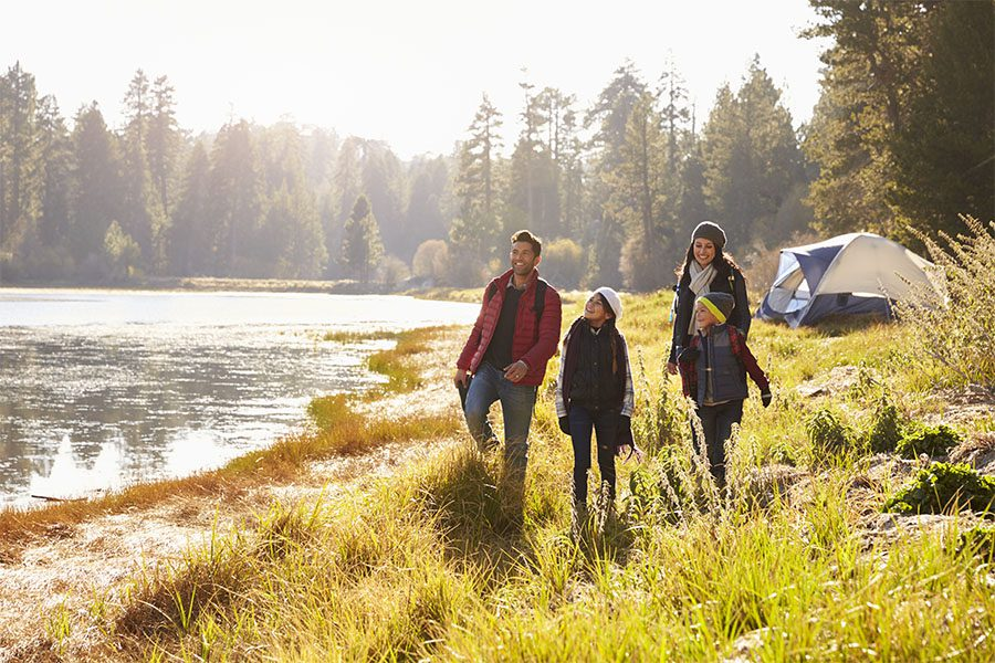 About Our Agency - Parents and Two Children on a Camping Trip Walking near a Lake on a Sunny Day