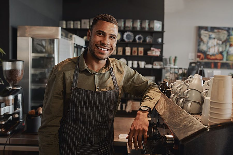Business Insurance - Portrait of Male Business Owner behind the Counter of a Small Restaurant and Smiling While Looking at the Camera