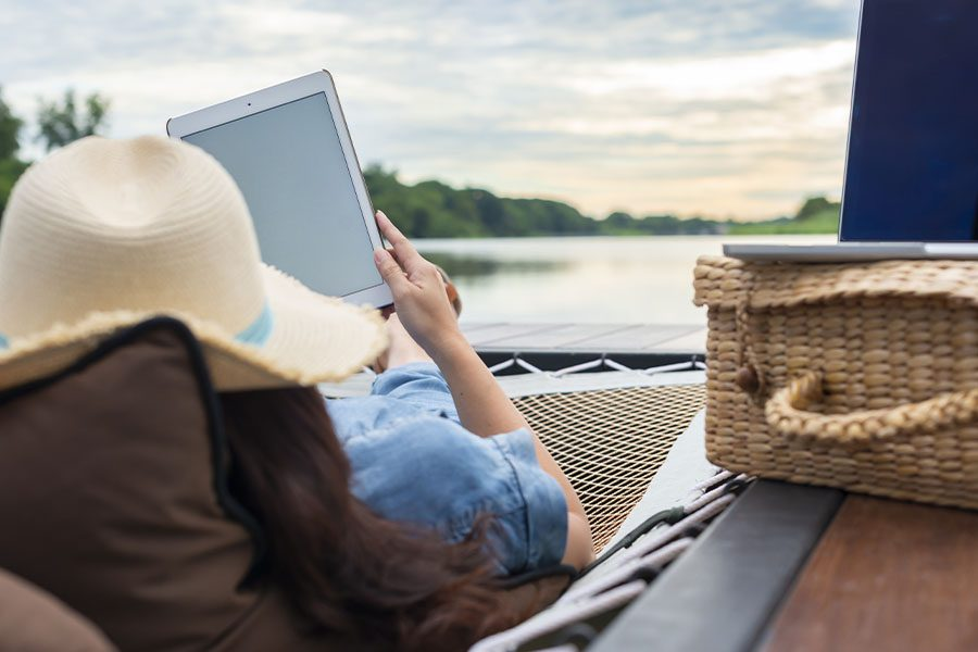 Client Center - Woman with a Laptop and Tablet Working Remotely While on a Hammock and Enjoying a Lake View at Dusk
