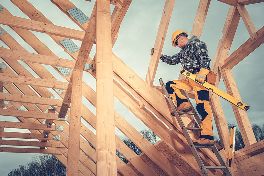 Specialized Business Insurance - View of Construction Worker Holding a Level and Working on the Frame of a House While Standing on a Ladder