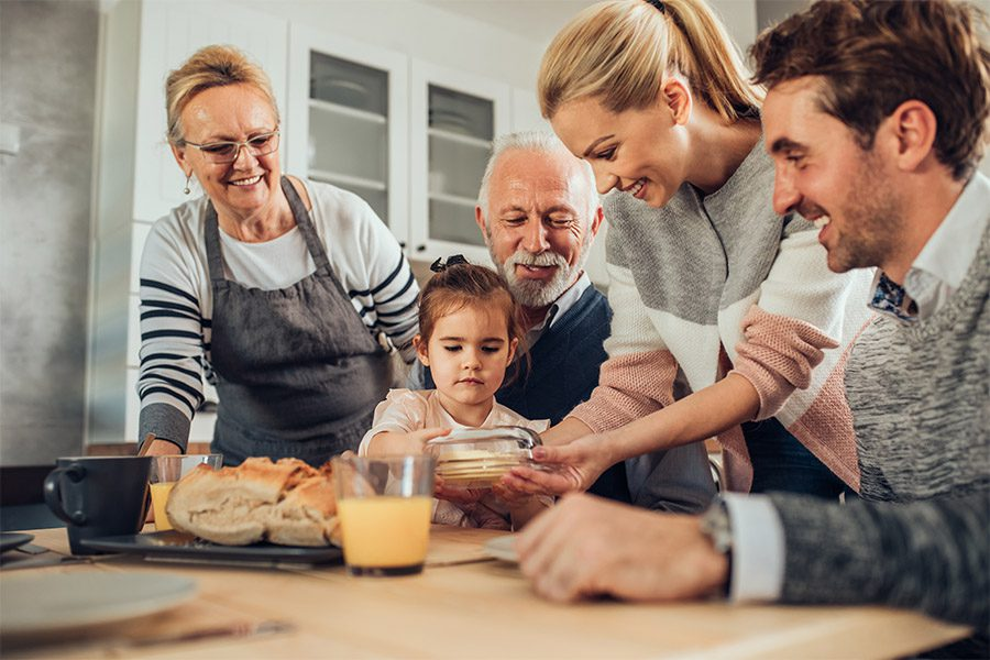WA State Long Term Care Act - Family Sitting in Kitchen Eating Food and Smiling