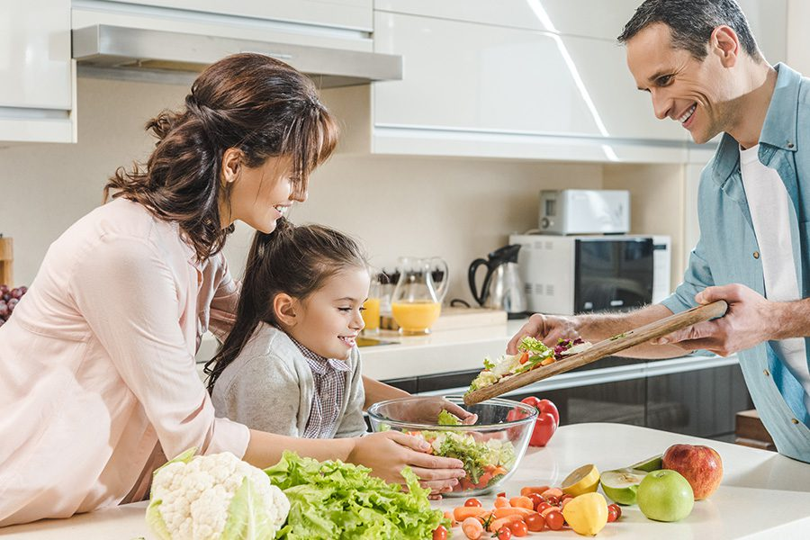 Personal Insurance - Happy Smiling Family Making Salad Together at the Kitchen