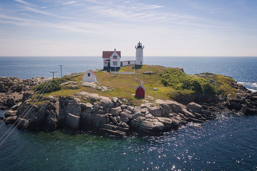 York, ME - View of Nubble Lighthouse Displaying The Ocean Around it on a Sunny Day
