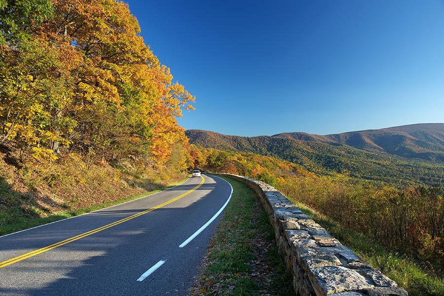 About Our Agency - Winding Road in the Shenandoah Mountains in Autumn, Bright Blue Sky Overhead
