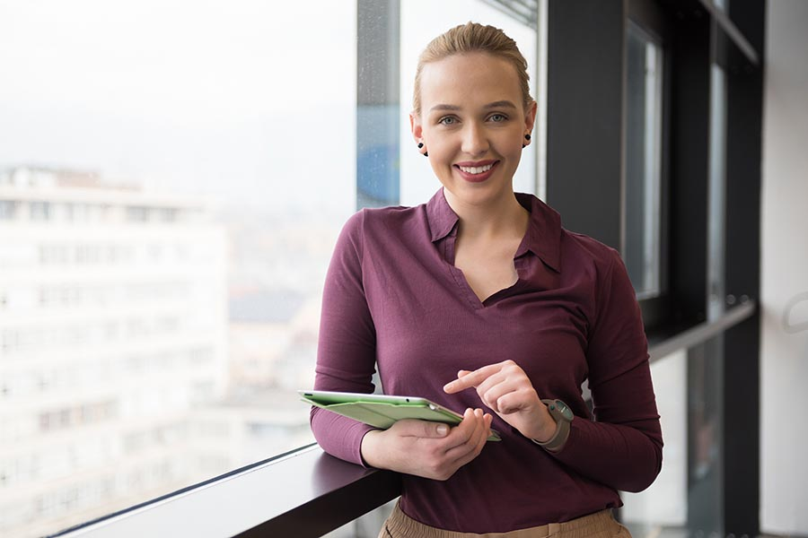 Business Insurance - Woman Stands by a Window in an Office Building Using a Tablet