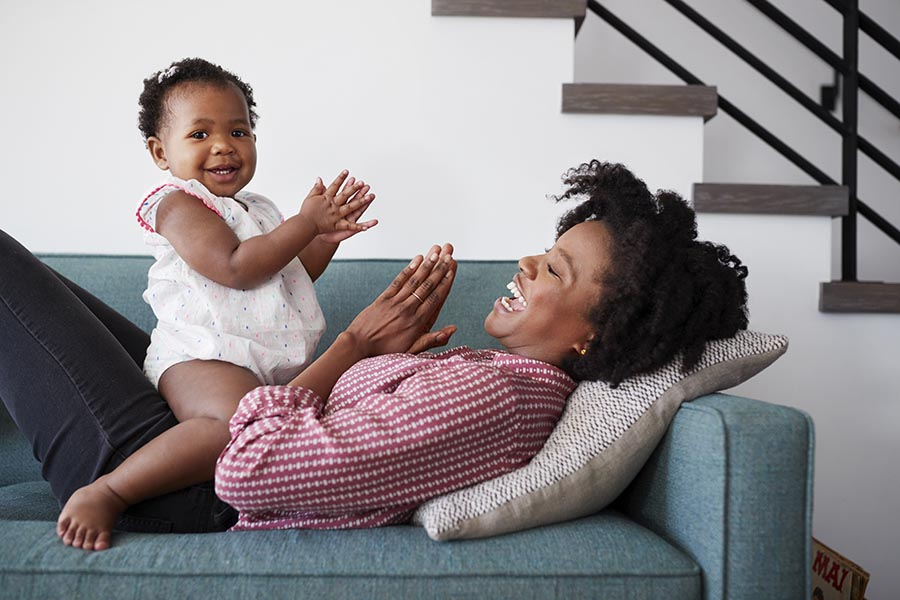 Personal Insurance - Mom and Baby Play Pat-a-Cake on Their Sofa, Baby on Mom's Lap, Both Smiling