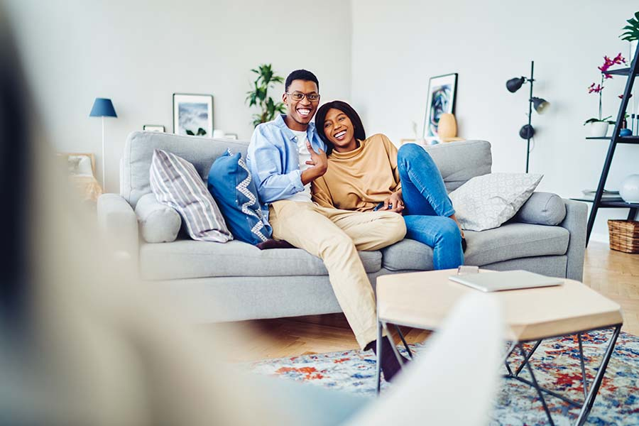 Personal Insurance - Happy Couple Resting Together and Sitting on the Sofa in the Spacious Living Room of Their Modern Apartment