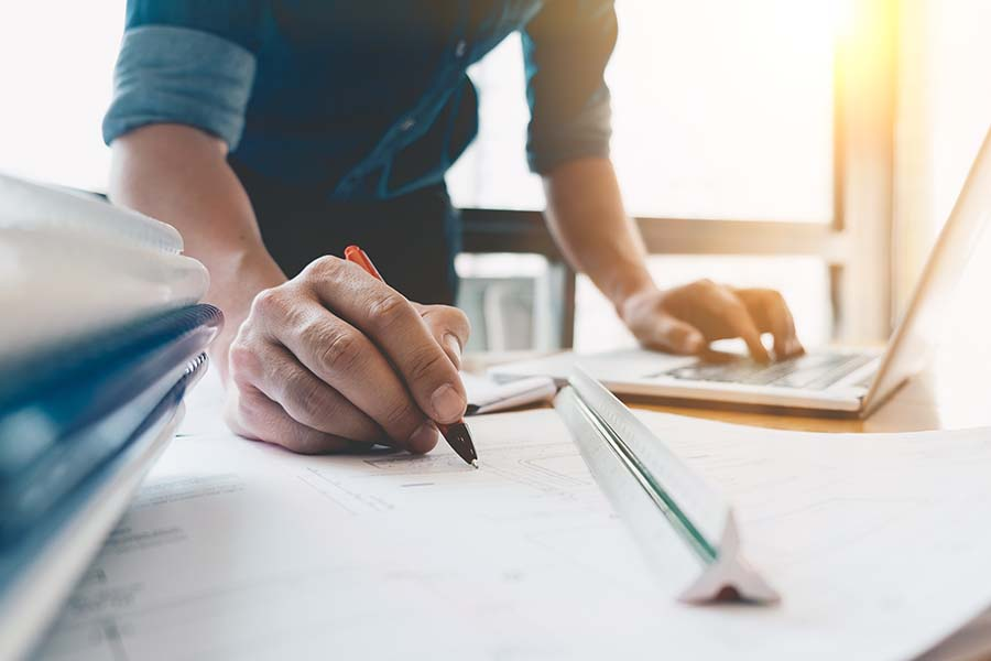Specialized Business Insurance - Closeup View of an Engineer Drawing a Blue Print of a Building in His Office