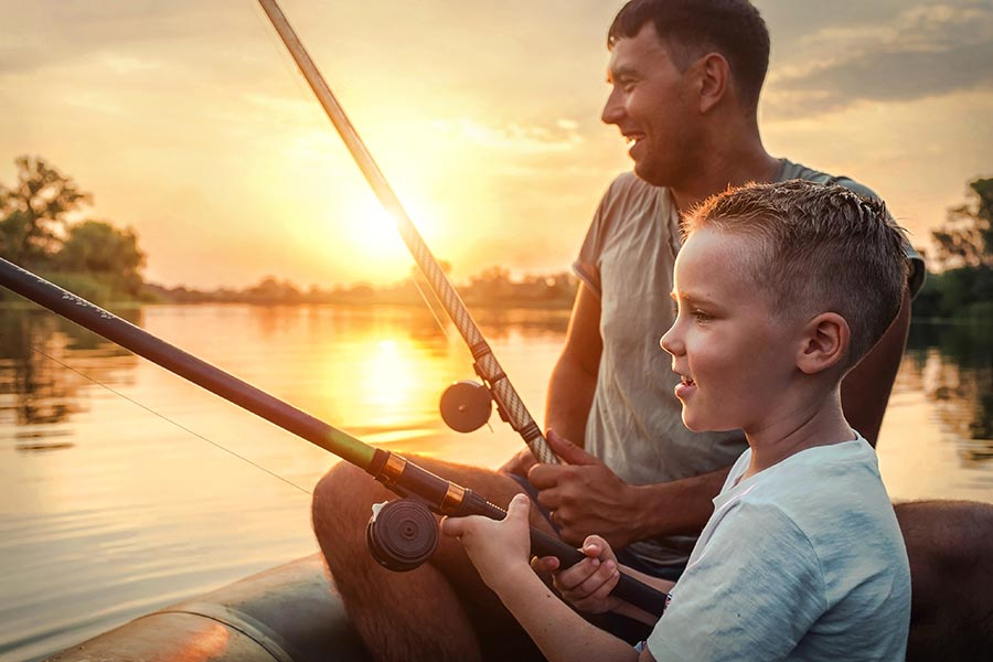 About Our Agency - Father and Son Fishing on a Lake at Sunset, Both Laughing