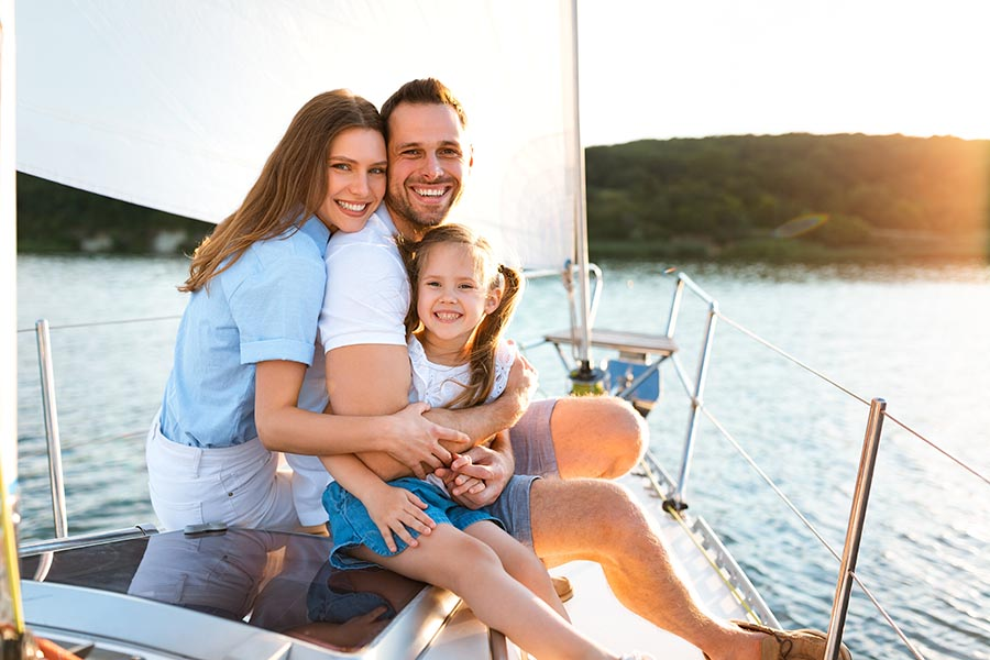 Personal Insurance - Mother, Father and Daughter Hug on a Sailboat With the Sun Shining on Them