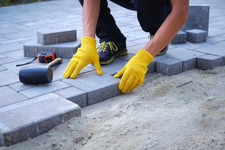 Specialized Business Insurance - Hardscaping Contractor Laying Stone for a Patio Over a Layer of Sand
