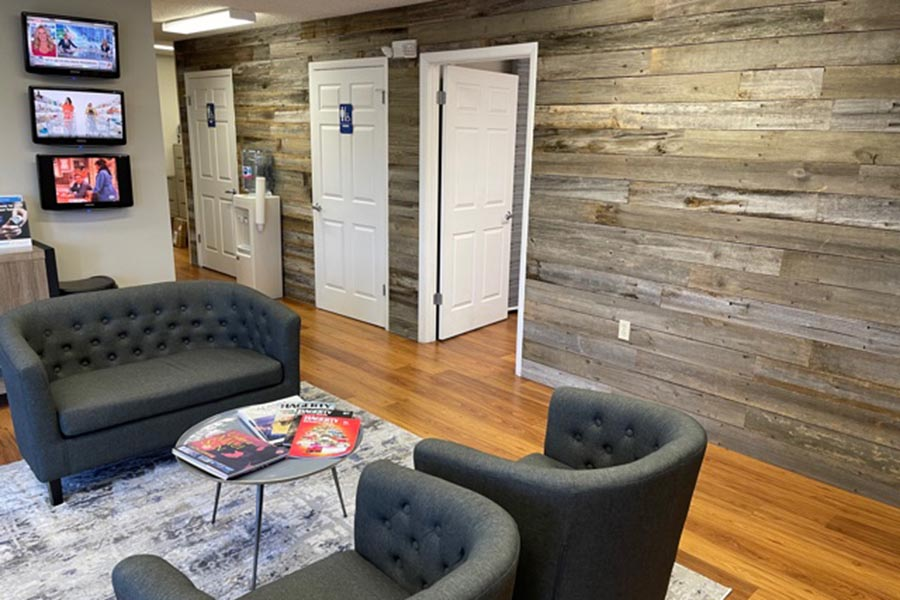 Contact - Bill Lovell Insurance Office Interior with Gray Furniture in a Waiting Area and Wood Paneled Walls
