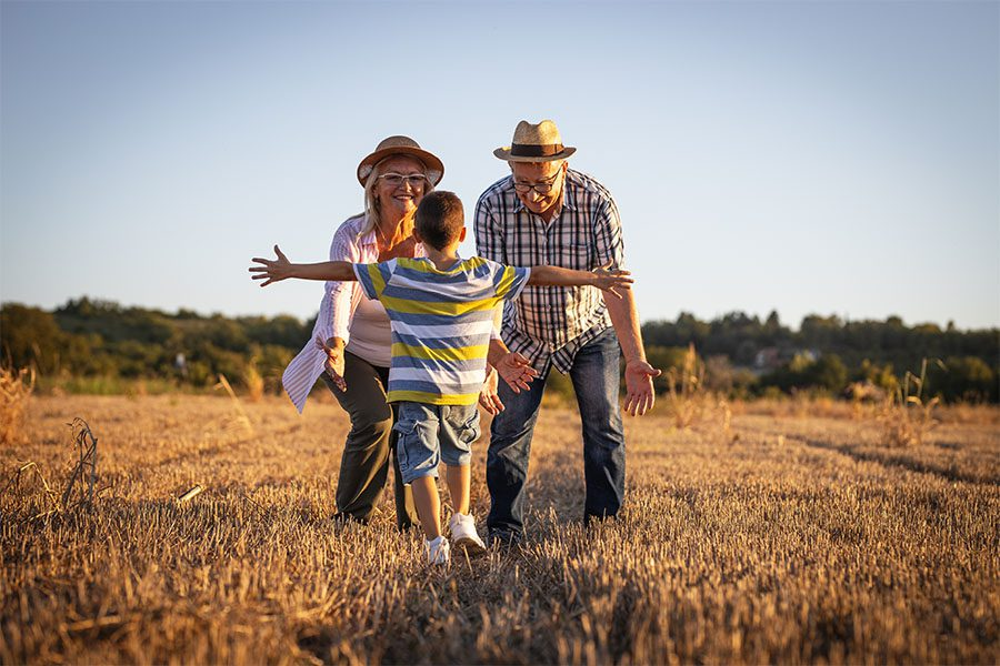 About Our Agency - View of a Young Boy Walking Up to His Grandparents While Holding His Arms Out for a Hug at Sunset on a Farm Field