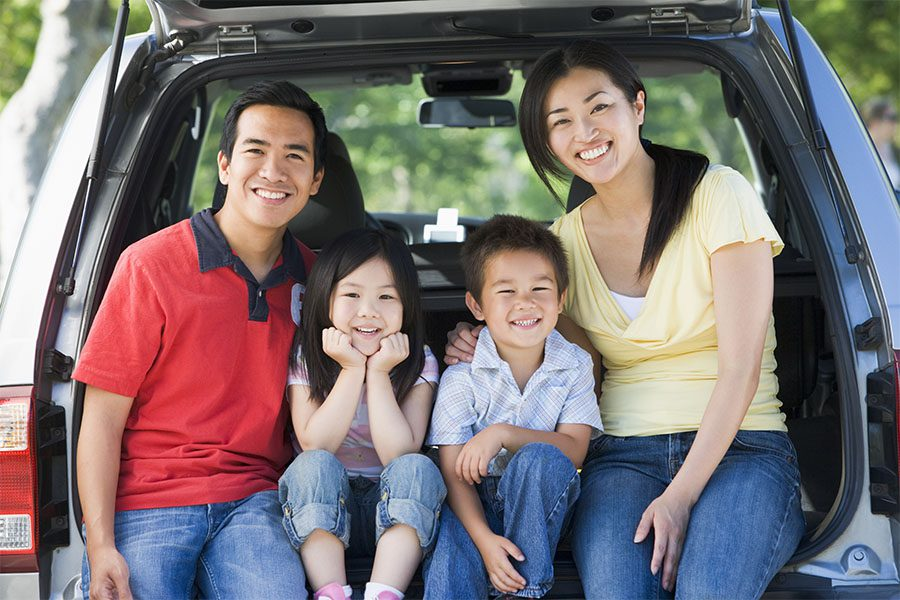 Blog - Portrait of a Cheerful Family with Two Young Kids Sitting in the Back Trunk of Their Car While Visiting the Park