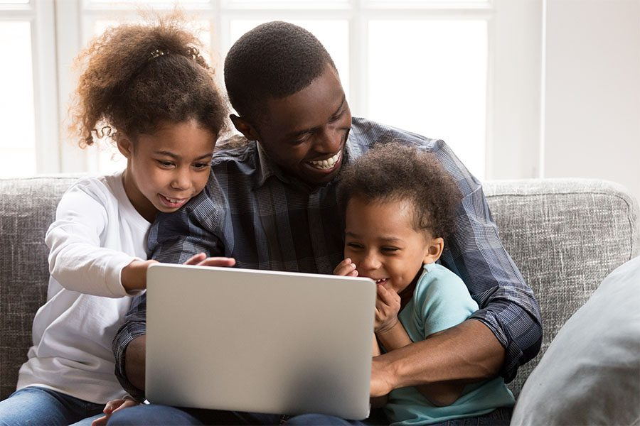 Client Center - Closeup Portrait of a Joyful Father and His Two Kids Sitting on the Sofa in the Living Room Having Fun Using a Laptop