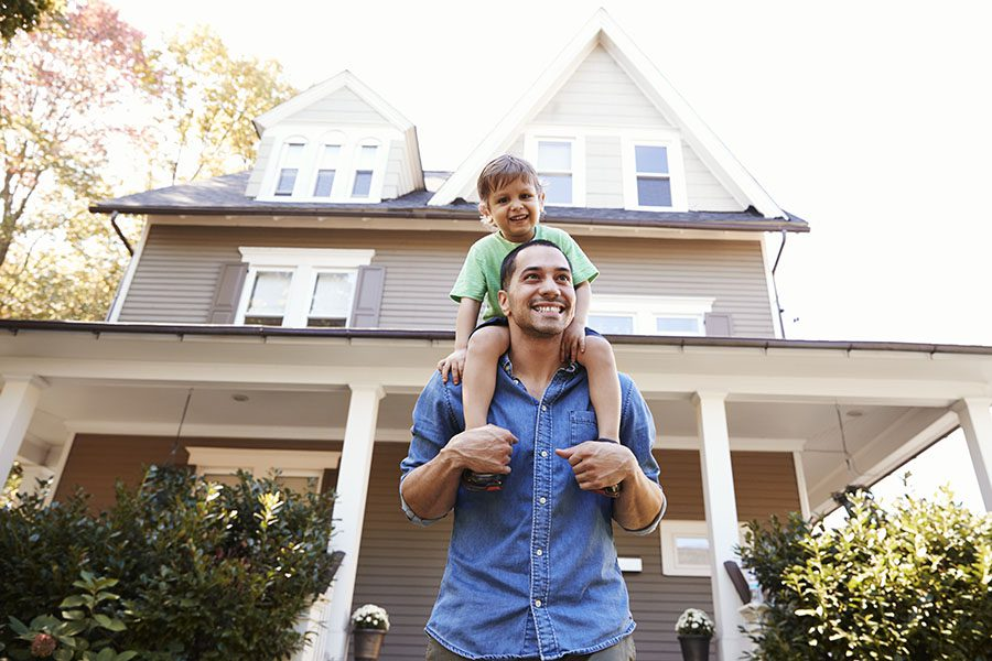 Personal Insurance - Portrait of a Cheerful Young Father Giving His Son a Piggyback Ride While Standing Outside Their Home