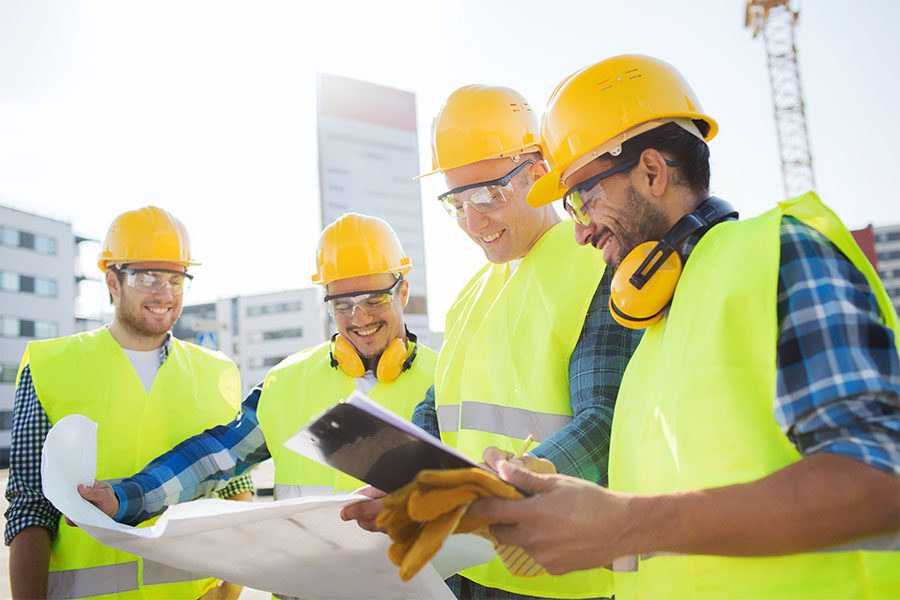 Specialized Business Insurance - Group of Smiling Contractors Standing Outside Looking at Blueprints and a Tablet to Plan Out Commercial Construction Project