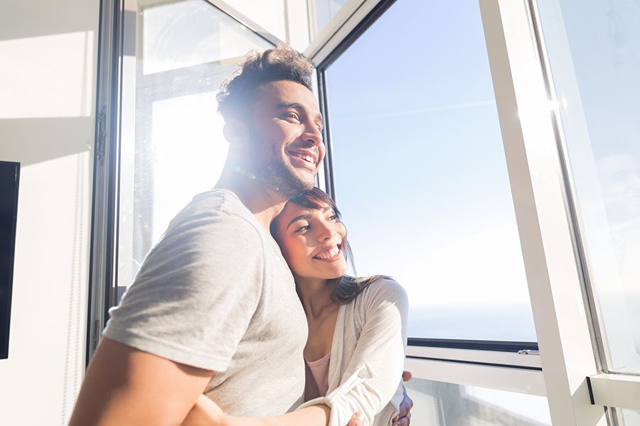 Personal Insurance - Happy Young Couple Looking Out the Window in Their Home