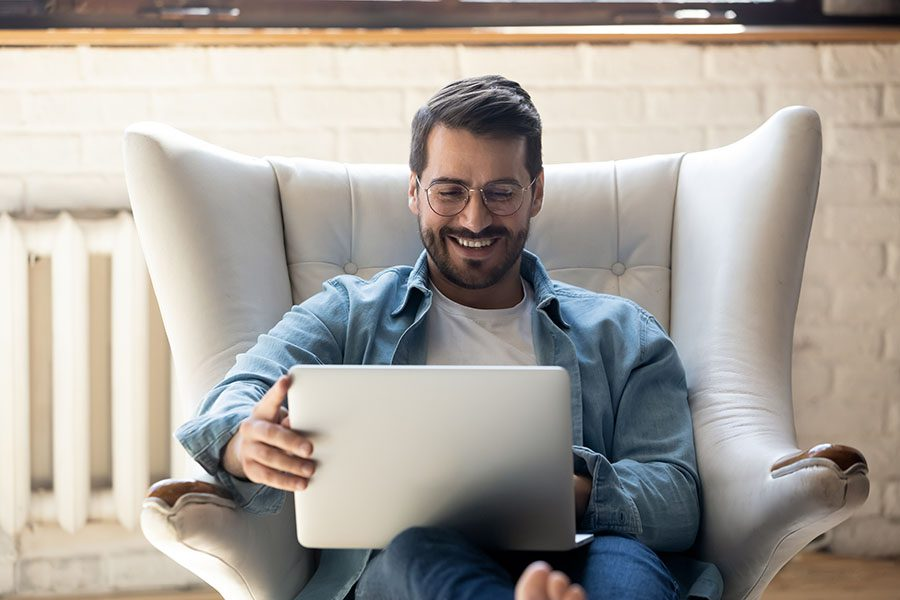 MassMutual FAQs - Portrait of a Smiling Man Sitting on a Lounge Chair Using His Laptop
