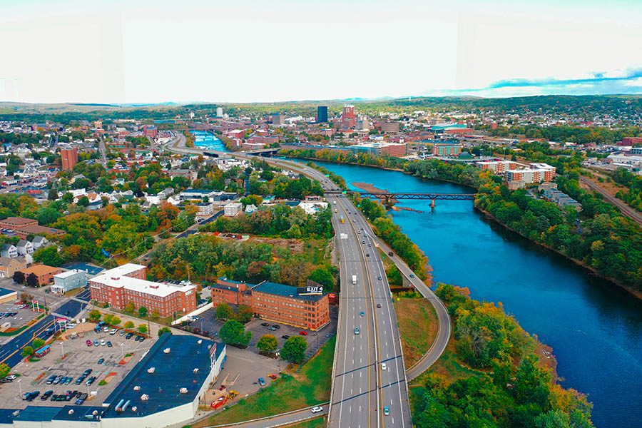 Bedford, NH Insurance - Aerial View of Bedford, NH in the Fall Above River and Highway