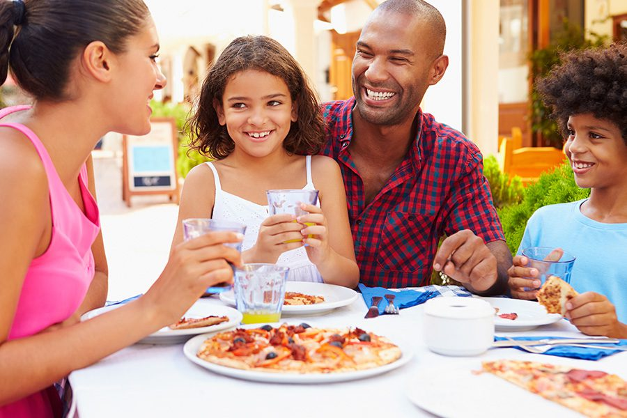 About Our Agency - Happy Family Having a Family Meal at a Outdoor Restaurant Together