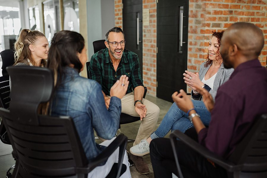 Employee Benefits - Group of Business People Sitting Together in a Circle in a Modern Office With Exposed Bricks Having a Casual Meeting
