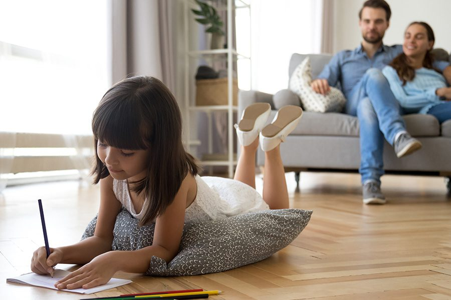 Personal Insurance - Father and Mother Sitting on a Sofa Together While Observing Their Daughter Draw Pictures on a Paper While Resting on a Pillow on the Floor