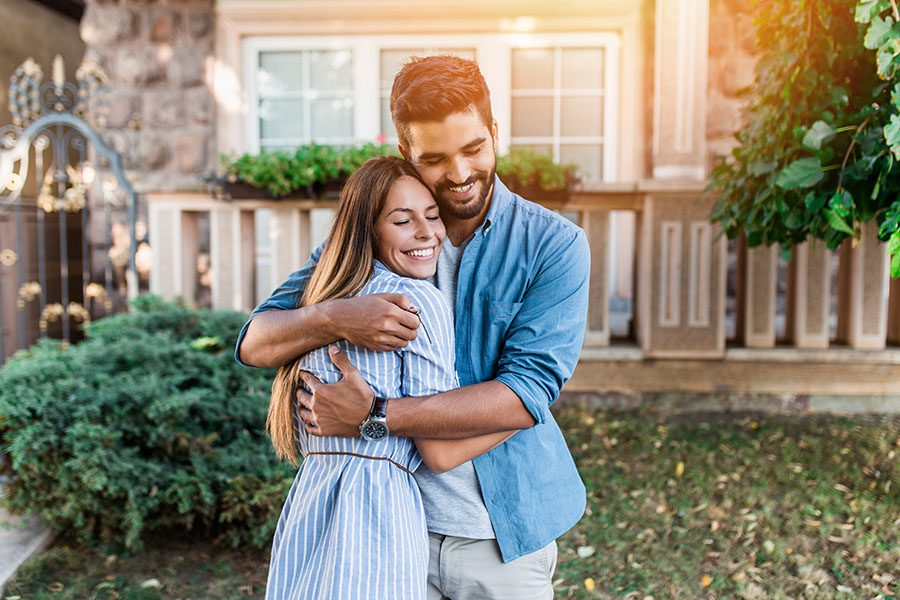 Personal Insurance - Portrait of a Happy Young Couple Hugging Each Other in Front of Their New Home
