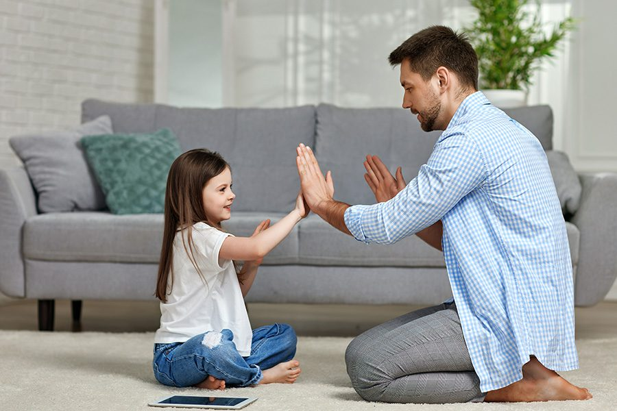 About Our Agency - Little Girl Plays Pattycake With Her Father on the Floor in Front of the Sofa