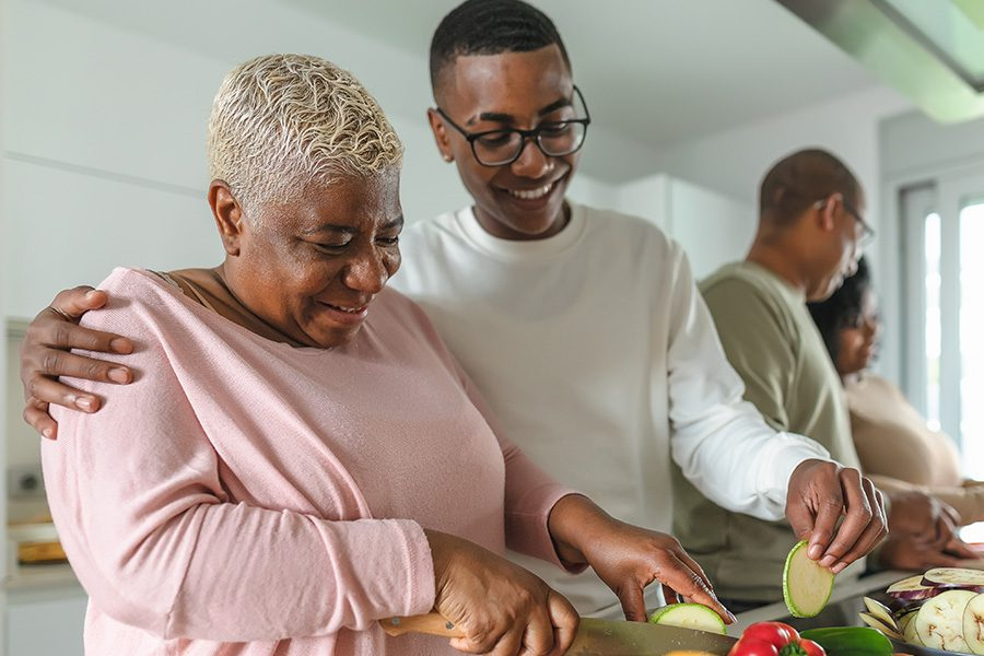 Employee Benefits - Family Having Fun in a Modern Kitchen Preparing Food Recipe With Fresh Vegetables