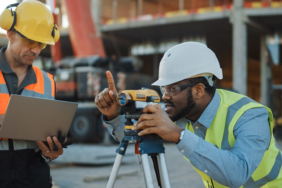 Specialized Business Insurance - Professional Engineer Surveyor Takes Measurements with a Theodolite While Another Worker Standing Near Him Uses a Laptop