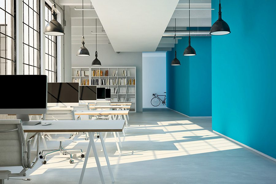 Business Insurance - View of Modern Open Architecture Office With Blue Walls and Computer Desks Near the Windows
