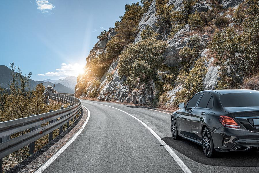 About Our Agency - Black Luxury Car Driving along a Mountain Highway, Rocky Ledge to the Right, Greenery to the Left