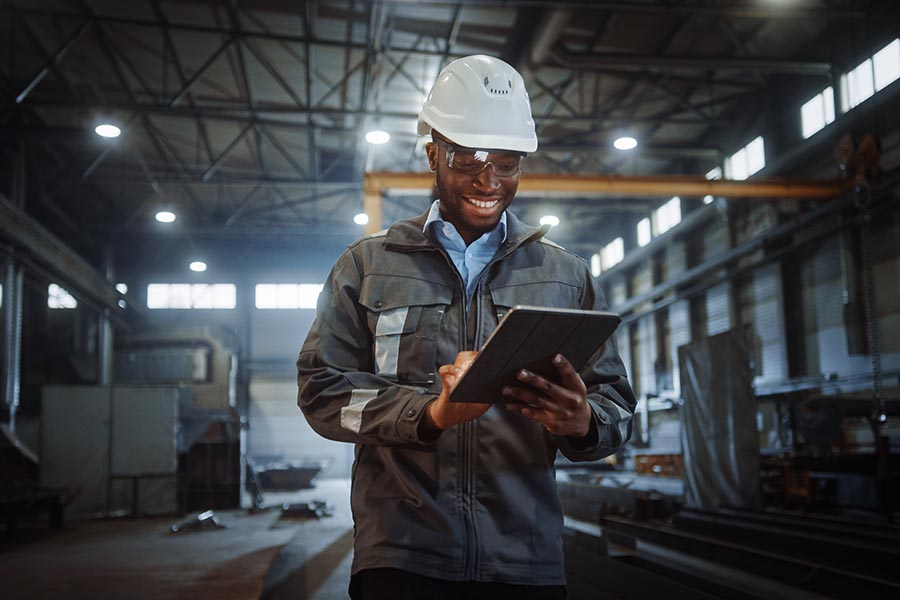 Client Center - Construction Engineer Smiling and Using a Tablet in a Warehouse, Hard Hat On