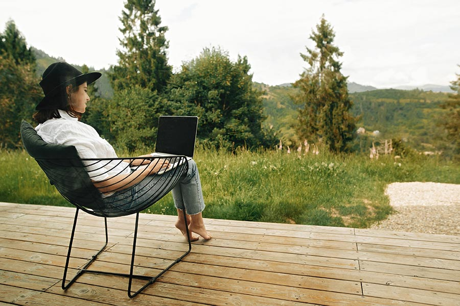 Contact - Woman Sitting in a Patio Chair on a Wooden Deck Overlooking a Beautiful Wooded Area, Using a Laptop