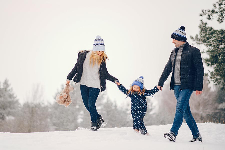 Personal Insurance - Family Walking through the Snow Holding Hands, Mom Holding Child's Teddy Bear