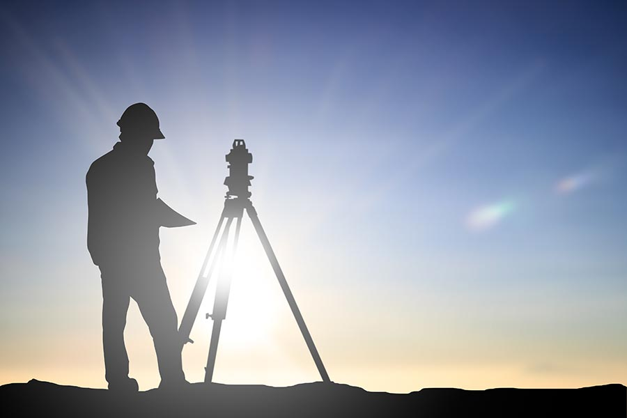 Specialized Business Insurance - Land Surveyer Stands in Silhouette against a Blue Sky with the Sun Shining