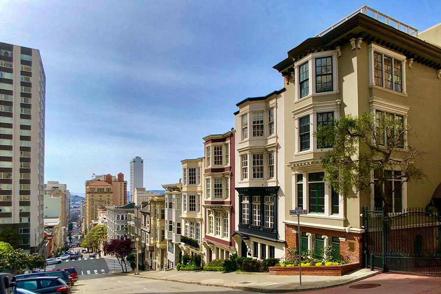 About Our Agency - Residential Street in San Francisco, California, Street Sloping Down a Hill, Skyline in the Distance