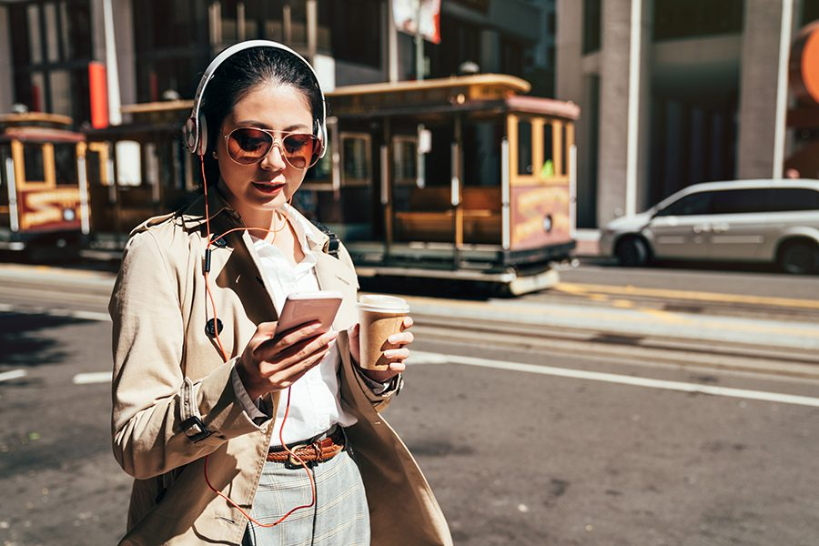 Client Center - Woman Walking Through San Francisco, Past Cable Cars, Wearing Headphones and Sunglasses and Uses Her Phone