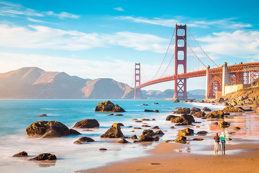 Contact - Golden Gate Bridge in San Francisco, California on a Sunny Day, Seen From the Beach, Large Rocks on the Shoreline and Mountains in the Distance