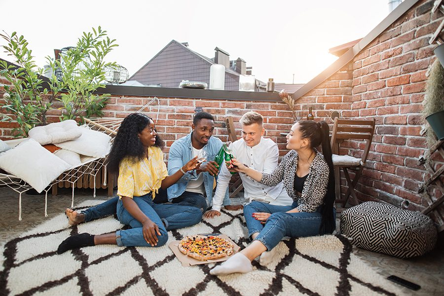 Personal Insurance - Couples on a Rooftop Deck, Brick Walls Around Them, Sitting on an Outdoor Rug Eating Pizza