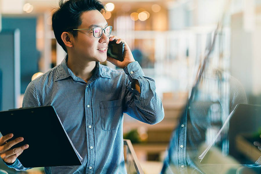 Business Insurance - Business Owner Smiling and Using One Hand to Hold His Smartphone While Woking in an Office