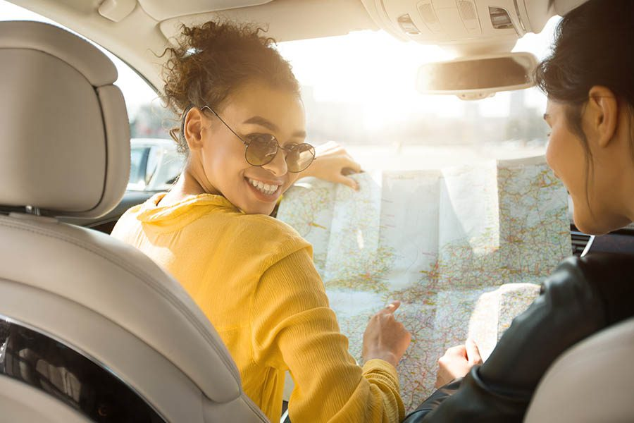 Personal Insurance - Happy Girlfriends Looking at a Map While Sitting in Their Car Before Taking a Road Trip