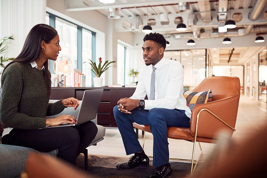 Business Insurance - Businesswoman Interviewing a Job Candidate for a Job Opening in the Seating Area of a Modern Office
