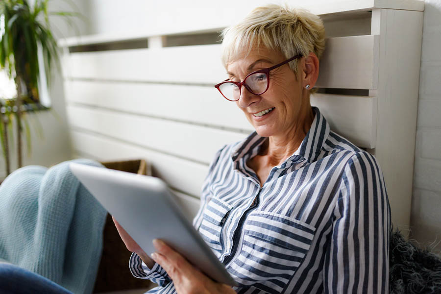 Client Center - Closeup Of a Smiling Senior Woman Using Digital Tablet at Home on the Sofa