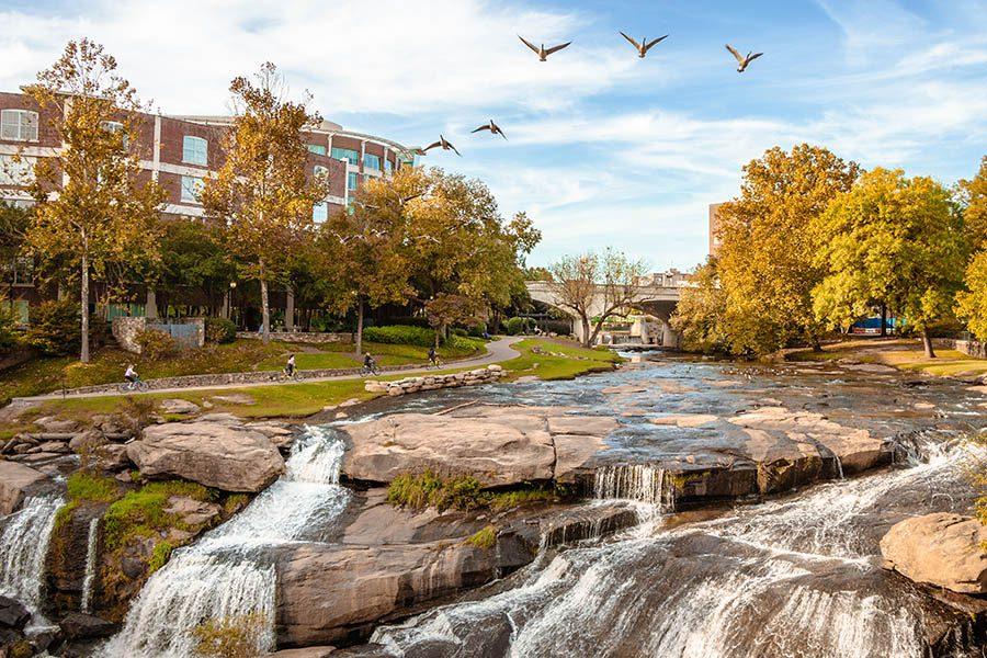 Contact - Picturesque View of River City in Greenville, South Carolina with Birds at Dusk
