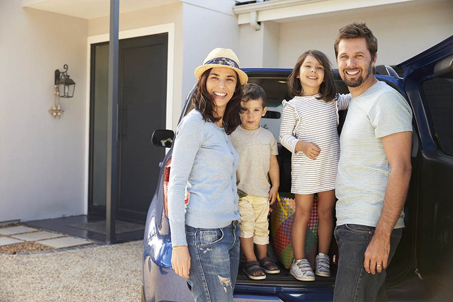Personal Insurance - Portrait of Family Standing in Front of Their Home and Packing Their Car to Get Ready For a Summer Vacation