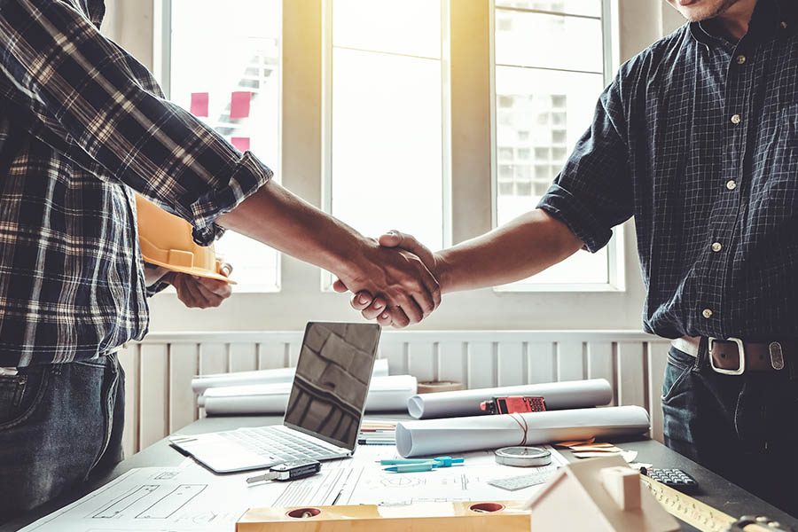 Specialized Business Insurance - Closeup Of Engineer and Contractor Shaking Hands on the Success of a Contracting Project They Worked on Together