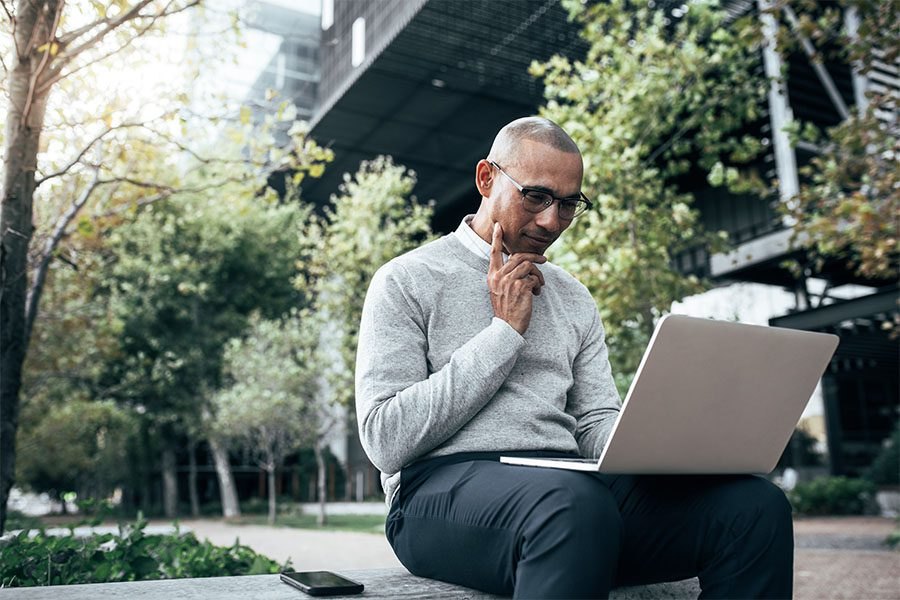 Blog - Portrait of a Young Businessman Sitting Outside of an Office Building Surrounded by Green Foliage Using a Laptop